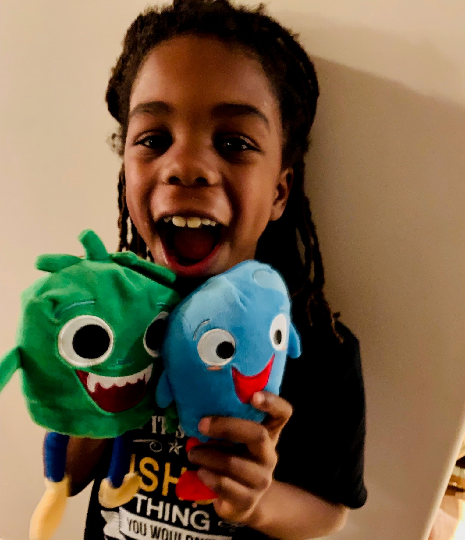 boy smiling with sqooasha plush toy
