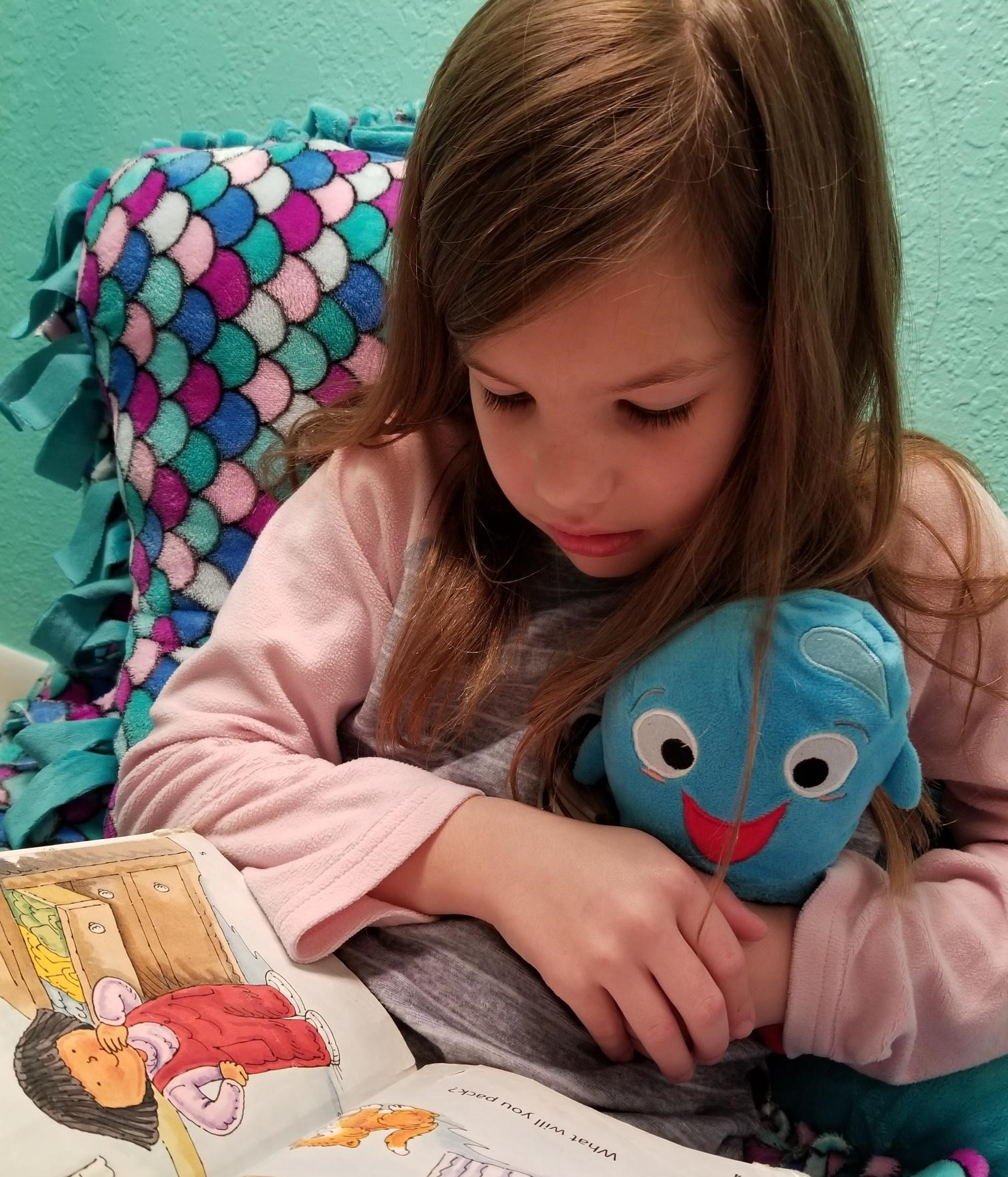 Girl reading with her Sqooasha plush toy